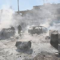 Firefighters put out a blaze after Syrian regime forces reportedly dropped barrel bombs Thursday on a rebel-held district of the city of Aleppo. | AFP