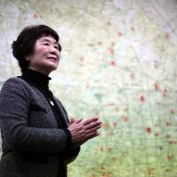 Haruyo Nihei speaks in front of a map illustrating damage inflicted on areas of Tokyo during the 1945 firebombings at the Center of the Tokyo Raids and War Damage on March 1. Nihei was only 8 years old when the biggest attack of World War II in Japan, the firebombing of central Tokyo, killed over 100,000 people and left hundreds of thousands more homeless. She fled with her family and watched as many others were burned alive. As the flames swept over her, she was sheltered by her father and many others who piled on top of them, some of whom suffocated or were burned to death. | AP