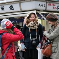 Foreign tourists visit the Nakamise shopping street in Tokyo's Asakusa district on Tuesday. | AFP-JIJI