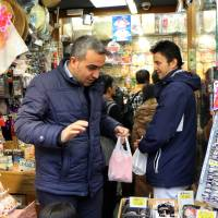 Foreign tourists visit a store on the Nakamise shopping street in Tokyo's Asakusa district on Tuesday. | AFP-JIJI