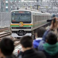 Railway fans await an incoming train on the Ueno Tokyo Line at JR Okachimachi Station in Tokyo on Saturday, the day of the launch of services enabling easier access between the capital and neighboring prefectures to the north such as Fukushima, Tochigi and Gunma.   KYODO