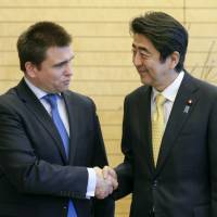 Ukrainian Foreign Minister Pavlo Klimkin is greeted by Prime Minister Shinzo Abe at the start of their talks in Tokyo on Monday.   AFP-JIJI