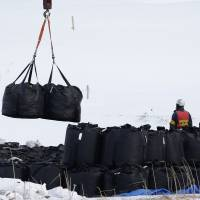 Bags of radiation-tainted soil are moved by a machine in Iitate, Fukushima Prefecture, in March 2014. The government plans to ratchet up its publicity campaign on the need to build permanent disposal sites for nuclear waste after being criticized for promoting nuclear power without already having such storage facilities in place. | BLOOMBERG