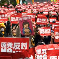 Protesters hold up placards at a rally Sunday in Tokyo to denounce atomic power plants. | AFP-JIJI