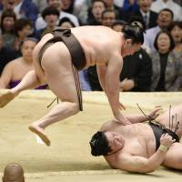 Watch out below: Hakuho, left, defeats Terunofuji on Wednesday. | KYODO
