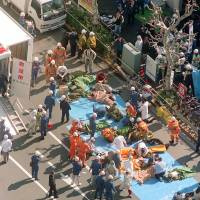 Underground attack: Medical personnel treat victims of the sarin gas attack outside Tsukiji Station in Tokyo's Chuo Ward on March 20, 1995. | KYODO