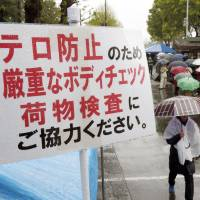 Rain check: A sign asks people to cooporate with body checks at a security perimeter that was set up for a marathon in Tokyo in April 2013. | KYODO