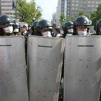 Police officers wearing protective gear stand guard during a protest against the Group of Eight summit in Sapporo in July 2008. | BLOOMBERG