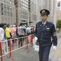 A police officer walks past runners before the start of the Tokyo Marathon in February. | KYODO