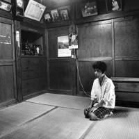 Unforeseen consequences: The widow of a taxi driver who was murdered by an American serviceman sits in her house in Koza on May 15, 1972, the day Okinawa reverted to Japanese control. | BUNYO ISHIKAWA