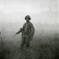 A U.S. soldier approaches a village in Binh Dinh's An Lao Valley at dawn in 1966. | BUNYO ISHIKAWA