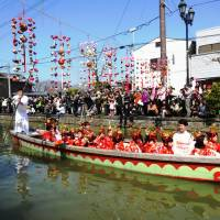 A boat in Yanagawa's living doll parade drifts under the sagemon. | MANDY BARTOK
