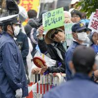 Looking for release: Protesters demonstrate outside the police station in Nago after the arrest of anti-base campaign organizer Hiroji Yamashiro. | KYODO