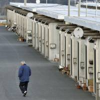 Stuck in time: A man walks past a row of temporary houses in Fukushima Prefecture on March 10.   KYODO