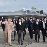 Show of force: Prime Minister Shinzo Abe inspects a mockup F-35A fighter jet on an air base in Omitama, Ibaraki Prefecture, last October. | AFP-JIJI