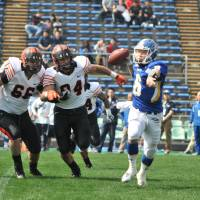 Under pressure: Princeton defensive lineman Henry Schlossberg (66) and linebacker Birk Olson (94) chase Kwansei Gakuin quarterback Mitsuhiro Izu during the first quarter of the Legacy Bowl on Saturday. | HIROSHI IKEZAWA