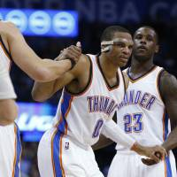 Masked avenger: Russell Westbrook is helped up during the third quarter of the Thunder's win over the Timberwolves on Friday. | AP