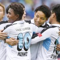 Off and running: Members of Kawasaki Frontale celebrate after a goal in the first half of their win over Yokohama F. Marinos on Saturday. | KYODO