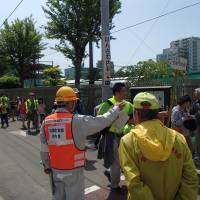 Volunteers in a disaster prevention community group direct people in a disaster drill.   SENDAI CITY