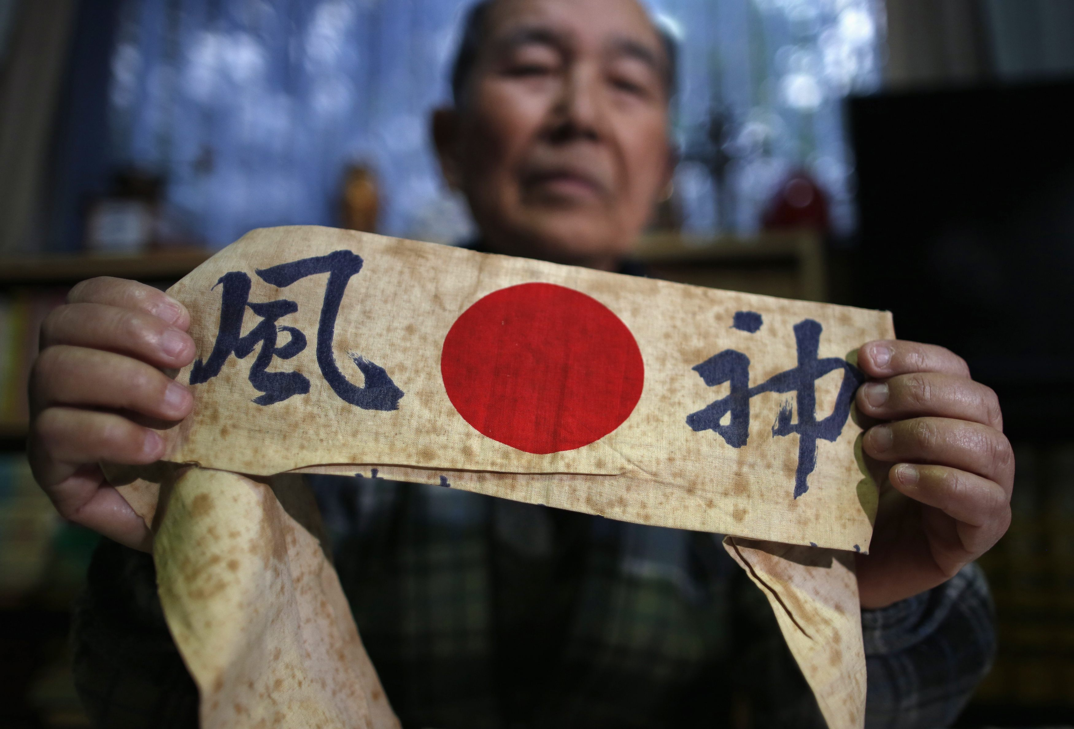 Author Katsumoto Saotome, 82, a survivor of the Great Tokyo Air Raid in 1945, holds a headband with the word 'kamikaze' on it during an interview at his home in Tokyo last Wednesday. | REUTERS
