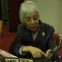 Michiko Kiyoka shows pictures of the family members she lost in the Great Tokyo Air Raid of March 10, 1945. | IAN MUNROE