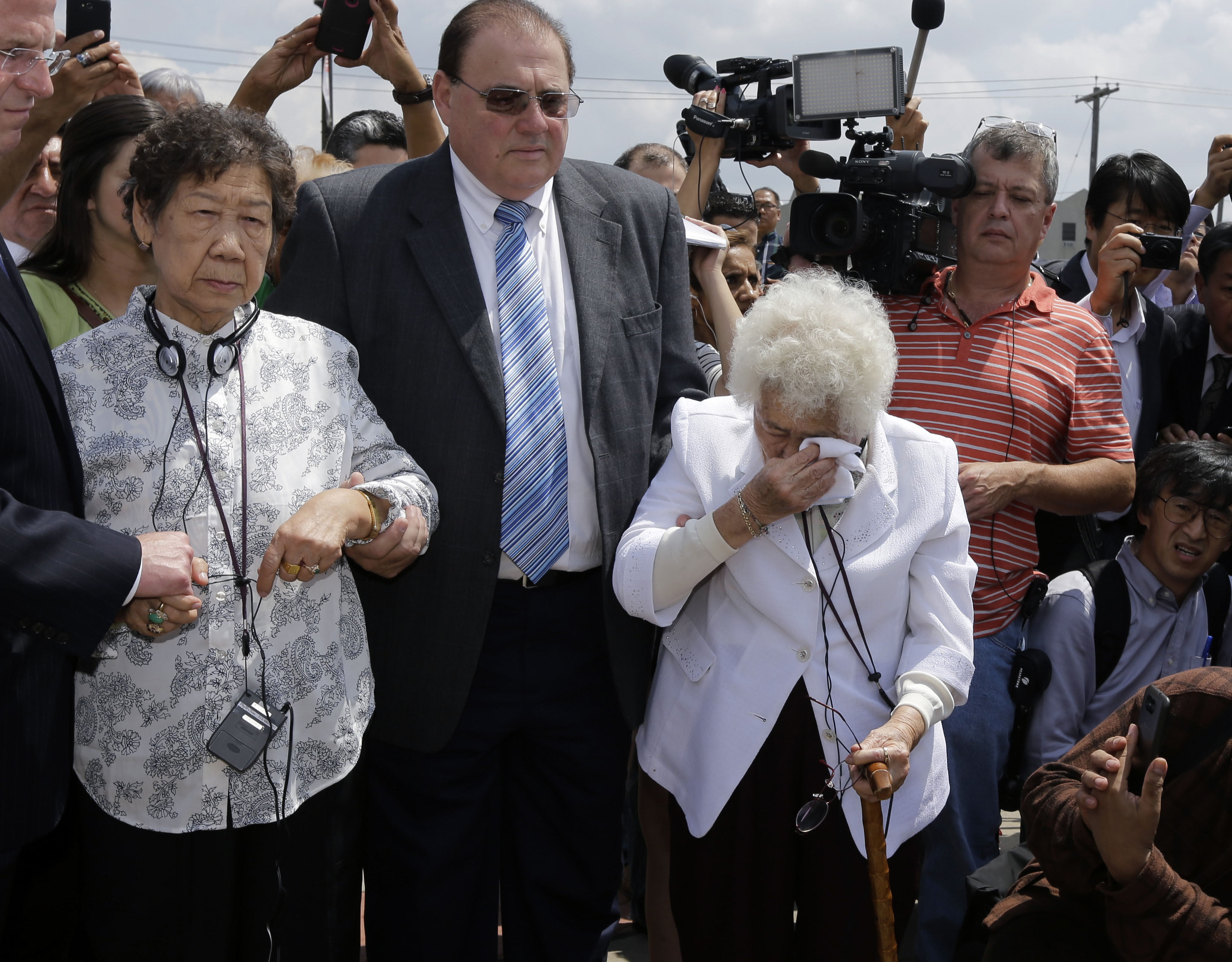 Remembrance: Ok Sun Lee, 87, wipes away tears as she stands with Il Chul Kang, 86, also a former 'comfort woman,' at the dedication in August of a monument in Union City, New Jersey, to the mostly Asian women who were forced into prostitution for Japanese forces in World War II. | AP