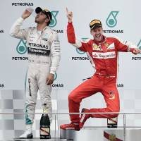 Jump for joy: Ferrari's Sebastian Vettel celebrates on the podium as Lewis Hamilton takes a drink of water after the Malaysian GP on Sunday. | AFP-JIJI