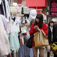 A woman uses her cellphone outside a clothing store in Tokyo's Harajuku district on March 23. The Bank of Japan kicked off radical monetary easing two years ago, but its target of 2 percent inflation has yet to be achieved. | BLOOMBERG