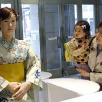 Customers watch android Aico Chihira during a reception held at Mitsukoshi Department Store in Tokyo on Monday. The lifelike robot, which was developed by electronics manufacturer Toshiba, began its first day at work as a receptionist at the department store. | AP