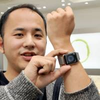 Customer Yoichiro Masui shows off his newly purchased Apple Watch. He was the first customer to secure one at SoftBank's Omotesando store in Tokyo on Friday morning. | YOSHIAKI MIURA
