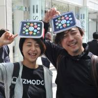 Shoppers Makoto Saito (left) and Kazumi Oda pose with cardboard Apple Watch hats outside SoftBank's Omotesando store on Friday. | YOSHIAKI MIURA