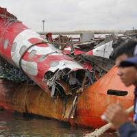 Security guards stand near the remains of the fuselage of the ill-fated AirAsia plane on the deck of a salvage ship at Tanjung Priok port in Jakarta on March 2. | AP
