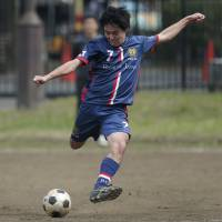 Bank of Japan staffer Yusuke Kumano (right), captain of the BOJ soccer club, shoots during an interbank soccer league match against Resona Bank Ltd. in Tokyo on March 28. | BLOOMBERG