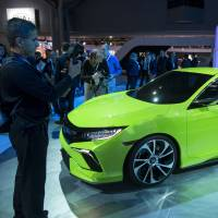 Journalists inspect Honda Motor Co.'s latest Civic concept car during its unveiling at the 2015 New York International Auto Show in New York on Wednesday. The 10th generation of the popular compact car will be 'dynamic, sporty and sophisticated,' Honda said. | BLOOMBERG