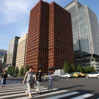Pedestrians walk past the Tokio Marine Holdings Inc. headquarters (center) in Tokyo in 2008. Unlike some of its counterparts, that have been buying trophy properties in the United States and Europe, Tokio Marine is putting its money into funds that invest in real estate. | BLOOMBERG
