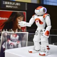A woman interacts with a Nao humanoid robot that offers basic service information in Japanese, English and Chinese at the Bank of Tokyo-Mitsubishi UFJ's flagship outlet in Tokyo on Monday. | KYODO