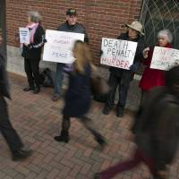 Pedestrians pass by protesters opposing the death penalty before closing arguments Monday in the trial of accused Boston Marathon bomber Dzhokhar Tsarnaev at the federal courthouse in Boston. | REUTERS