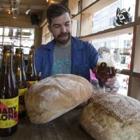 Sebastien Morvan, one of the founders of the Brussels Beer Project, examines a beer called Babylone, made from bread, at the Barbeton bar in central Brussels on Tuesday. | REUTERS