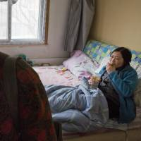 Chen Shuhong (left) walks out of the room she rents out to cancer patient Li Xiaohe (right) in Beijing on March 16. The so-called cancer hotels dot the neighborhood around China's most renowned cancer hospital. | AP
