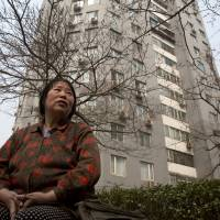 Chen Shuhong is interviewed in front of the residential compound where she rents out apartments as housing for cancer patients in Beijing on March 16. | AP