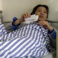 Shi Jieying talks from her bed after she was hospitalized with heart trouble in Zhongshan, in southern China's Guangdong Province, at the end of March. Earlier in the month, Shi joined fellow workers in a strike at the handbag factory where she worked. | AP