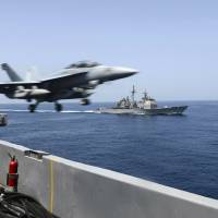 An EA-18G Growler launches from the flight deck of the aircraft carrier USS Theodore Roosevelt (CVN 71) with the guided-missile cruiser USS Normandy (CG 60) alongside during maritime security operations in the Arabian Sea in this U.S. Navy photo taken Tuesday.  The Roosevelt and Normandy will join seven other U.S. warships near Yemen, which is torn by civil strife as Iranian-backed Houthi rebels battle forces loyal to the U.S.-backed president. The warships are also keeping tabs on an Iranian flotilla that may be trying to bring arms to the Houthis. | REUTERS
