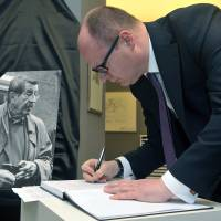 Pawel Adamowicz, mayor of Gdansk, Poland, signs a condolence book in memory of German writer Gunter Grass,  who was born in the city, previously Danzig, Germany, and died Monday at 87. | AP