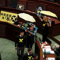 Pro-democracy lawmakers Raymond Chan (second right) chants slogans as he and Albert Chan (right), carrying yellow umbrellas, a symbol of the pro-democracy Occupy Central protest movement, leave to boycott Hong Kong Chief Secretary Carrie Lam during a Legislative Council meeting in the city Wednesday. The Hong Kong government unveiled a long-awaited electoral blueprint for selecting the city's next leader to lawmakers on Wednesday, in a plan that reflected China's desire for a tightly controlled poll that is likely to rile democracy activists. | REUTERS