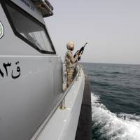 A Saudi border guard watches Wednesday from a boat off the coast of the Red Sea on Saudi Arabia's maritime border with Yemen, near Jizan. Iran sent two warships to the Gulf of Aden on Wednesday, state media reported, establishing a military presence off the coast of Yemen where Saudi Arabia is leading a bombing campaign to oust the Iran-allied Houthi movement.   REUTERS