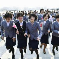 North Korean university students offer gifts of flowers during celebrations for Wednesday's birth anniversary of the country's founder, Kim Il Sung, at the Mansu Hill Grand Monument in Pyongyang. | KYODO