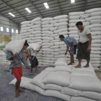 In this picture taken Jan. 13, workers carry heavy sacks of rice for export at a warehouse on the outskirts of Yangon. Despite many obstacles, Myanmar farmers are hoping to resurrect the country's reputation as Asia's premier rice producer. | AFP-JIJI