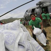 Nepalese volunteers on Monday unload relief materials delivered by an Indian Air Force helicopter at Trishuli Bazar, northwest of Kathmandu, for victims of last weekend's earthquake. Wedged between China and India, two rising Asian powers, landlocked Nepal saw rescuers and offers of help pour in from both sides within hours of the massive earthquake. | AP