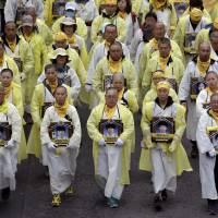 Relatives carrying portraits of victims in the sinking of the South Korean ferry Sewol march during an April 5 rally in Seoul demanding the ship be salvaged. | AP