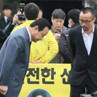 South Korean Prime Minister Lee Wan-koo bows as he is blocked by family members of the victims of the sunken South Korean ferry Sewol outside a remembrance hall in Ansan on Thursday. Grief, anger and political tension colored the first anniversary of South Korea's Sewol ferry disaster on Thursday, with complaints of continued official indifference toward the tragedy, which claimed 304 lives. | YONHAP / AFP-JIJI
